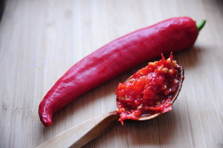 מחקר על ההשפעה של מזון חריף על חשק למלוח ומתוק: פלפל חריף וכף עץ עם מחית של פלפל