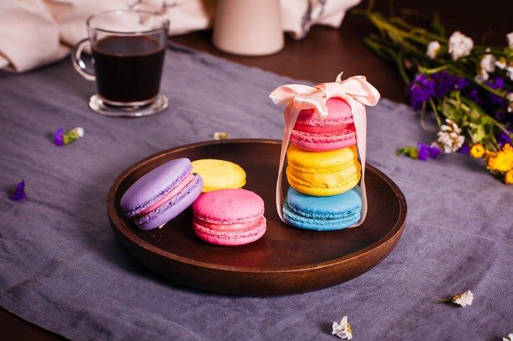 מחקר על ההשפעה של מזון חריף על חשק למלוח ומתוק: מקרונים צבעוניים מוגשים על צלחת לצד כוס קפה