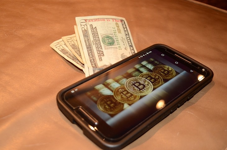 הסבר מהו הביטקוין: טלפון נייד ובו דימוי מטבעות ביטקוין ומתחתיו שטרות דולרים