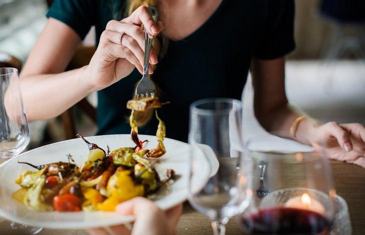 מחקר על ההשפעה של מזון חריף על חשק למלוח ומתוק: אישה מושיטה מזלג לצלחת אוכל