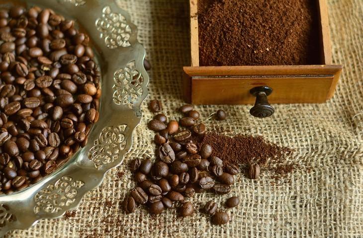תוספים מזיקים לוויטמינים ותוספי מזון: מגירה עם קפה טחון שוכבת על בד לצד פולי קפה