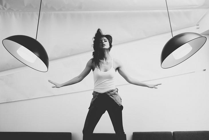 השפעת האישיות על הכושר הגופני: אישה רוקדת בסטודיו ליד אהילים תלויים