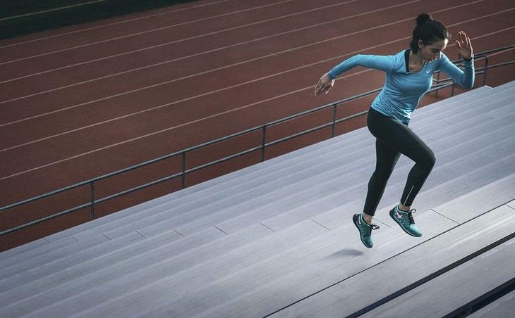 השפעת האישיות על הכושר הגופני: אישה מטפסת על מדרגות באיצטדיון אתלטיקה