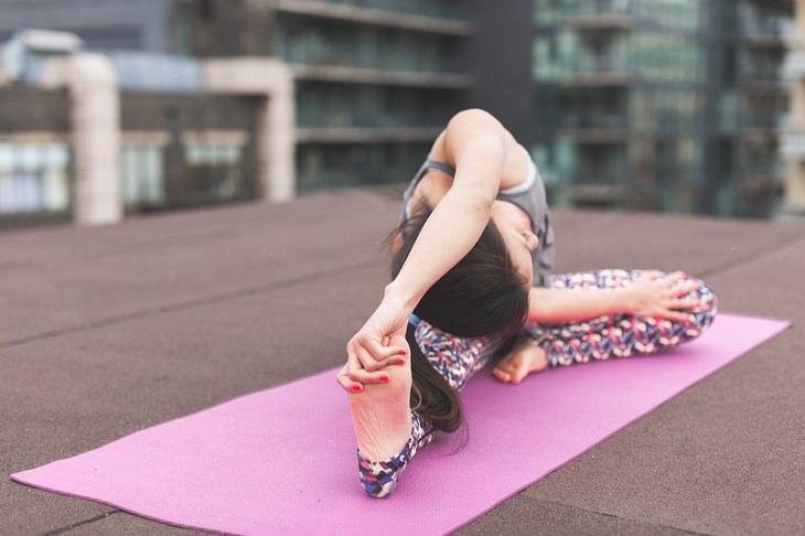השפעת האישיות על הכושר הגופני: אישה יושבת על מזרן ומותחת את גופה בתרגיל יוגה