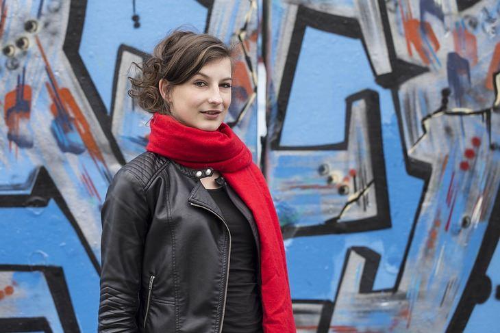 מידע שחייבים לספר לרופא: אישה כבת 40 על רקע קיר גרפיטי ברחוב