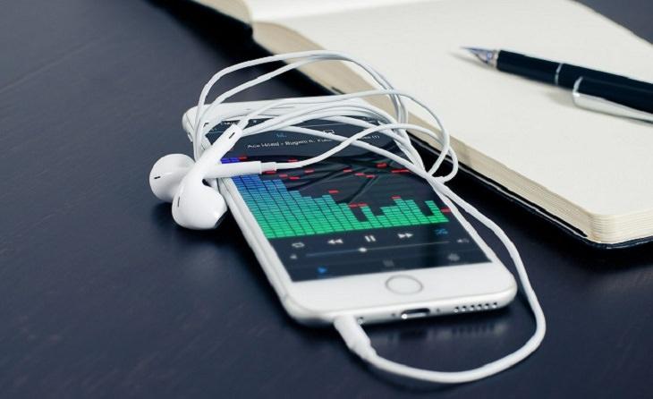טריקים לשיפור תפקידי המוח והגוף: סמארטפון עם אוזניות מונח על שולחן