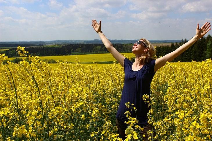 מתי עדיף להגיד תודה: אישה פורסת ידייה לשמיים בשדה פרחים