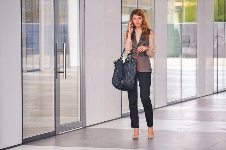 מתי עדיף להגיד תודה: אישה בחלל משרדים משוחחת בטלפון הסלולרי