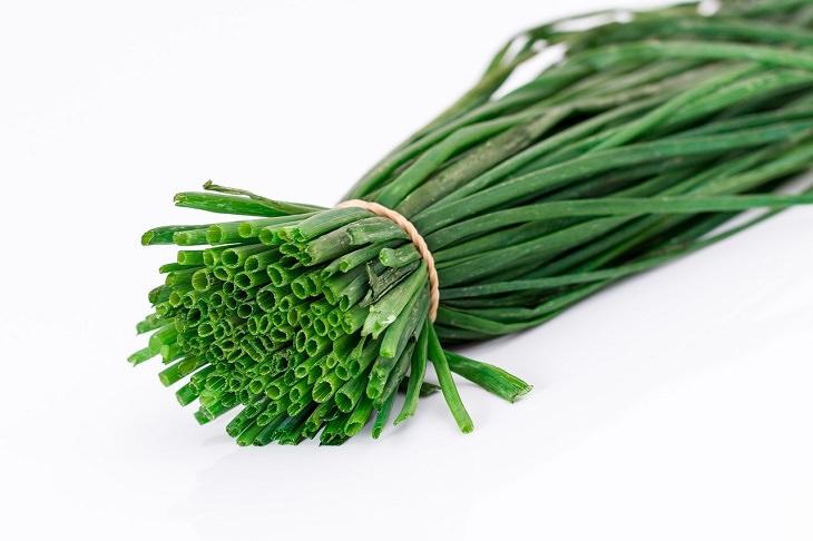 יתרונות בריאותיים של בצל ירוק: צרור בצל ירוק אסוף בגומיה