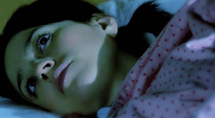 טעויות שמונעים מכם שינה ערבה: אישה שוכבת במיטה עם עיניים פקוחות