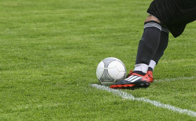 רגל בועטת בכדור על מגרש כדורגל
