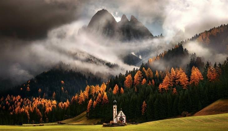 תמונות מדהימות: כנסייה על כר דשא והרים מכוסי ערפל