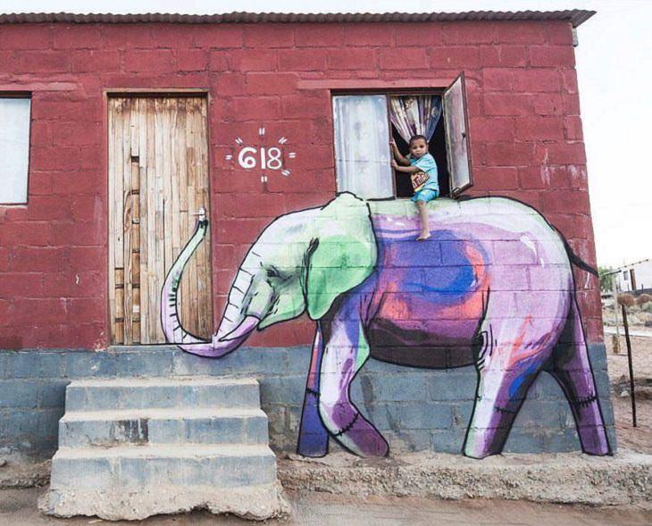 """אומנות רחוב מצחיקה: ציור קיר של פיל עליו """"רוכב"""" ילד אמיתי"""
