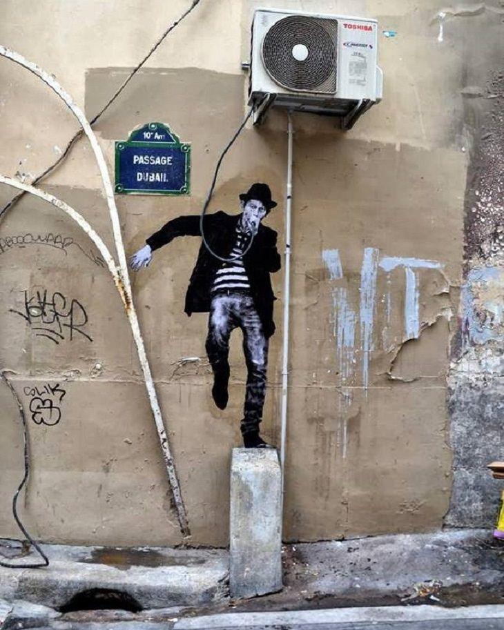 אומנות רחוב מצחיקה: ציור קיר של גבר השותה מצינור המזגן