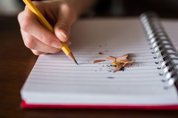 אשליות בחיים: יד של אדם מחזיקה עיפרון מעל מחברת