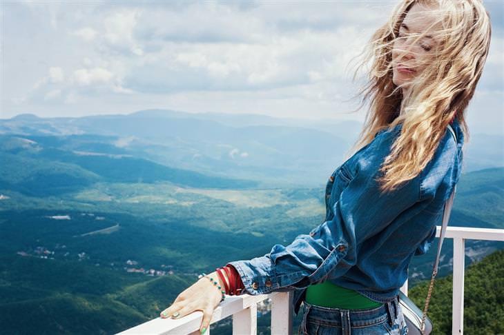 אשליות בחיים: אישה עומדת על מרפסת גבוהה מול נוף רחב וירוק