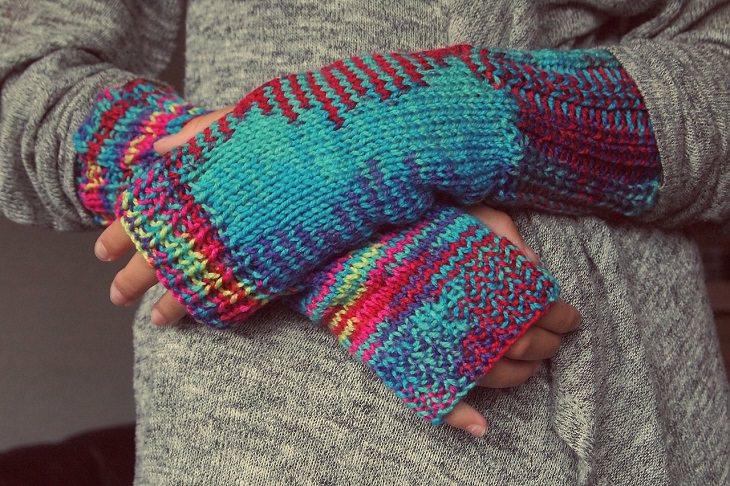 סריגה באצבעות וללא מסרגות: ידיים עוטות כפפות צמר שחושפות אצבעות