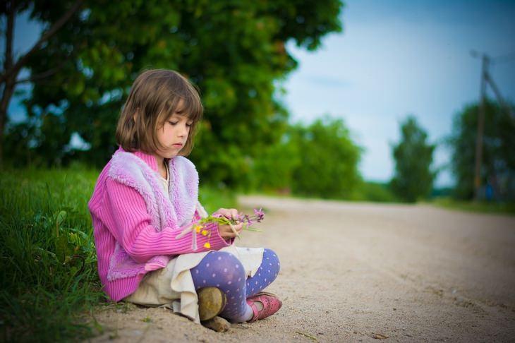 עצות הורות של סופר נני המקורית: ילדה יושבת ברחוב ומחזיקה פרחים בידה