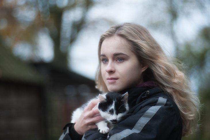 יתרונות הקמפור: נערה מחזיקה חתול בידה ברחוב, במזג אוויר חורפי