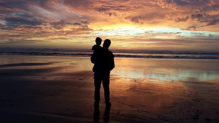 שאלות שכדאי לשאול את הילדים: צללית של אבא מחזיק ילד ביד בחוף הים מול השקיעה