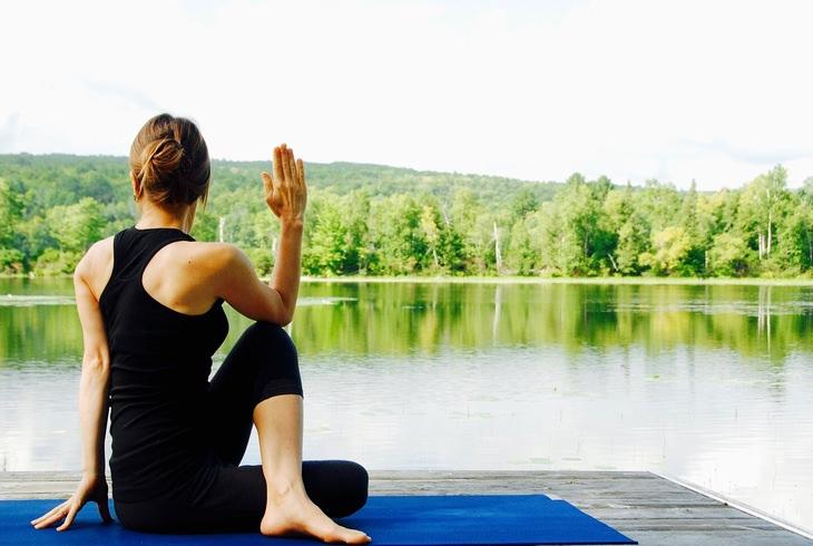 הבטחות לשנה הקרובה: אישה מתאמנת בתרגילי יוגה בסמוך לנחל