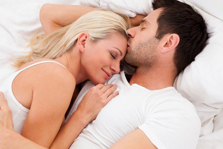 הרגלי שינה שמשפיעים על הזוגיות: זוג שוכב במיטה והגבר מנשק את האישה במצח