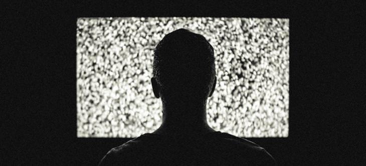 הרגלי שינה שמשפיעים על הזוגיות: צללית של איש מול טלוויזיה עם מסך מושלג