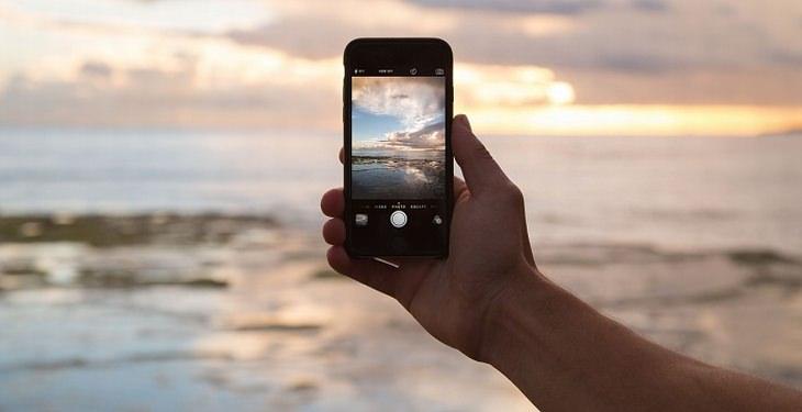 טיפים לעבודה עם המחשב: איש מחזיק סמארטפון מול הים