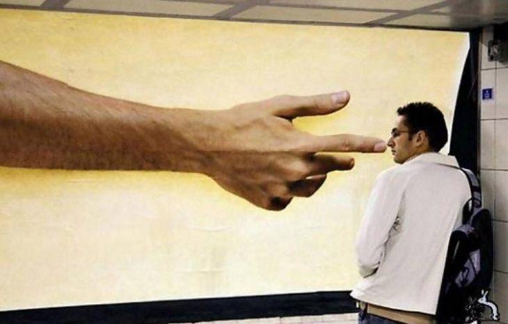 תמונות מצחיקות בתזמון מושלם: יד המופיעה על מודעת פרסומת יוצרת אשליה של חיטוט באף של גבר