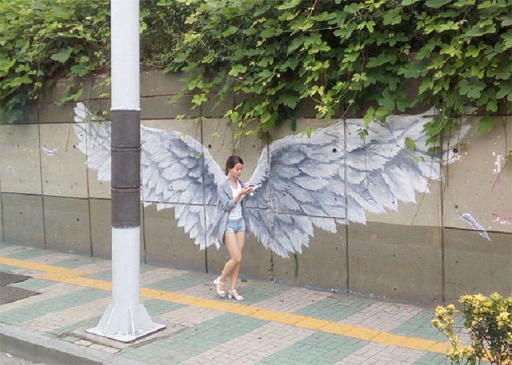 תמונות מצחיקות בתזמון מושלם: אישה חולפת ברחוב ליד ציור גרפיטי של כנפיים