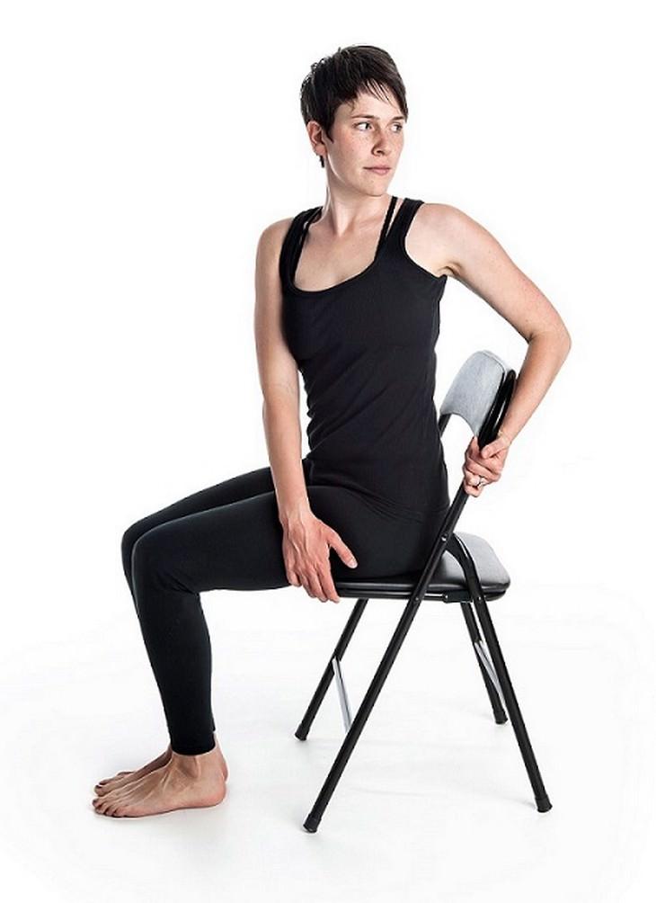 אישה נמתחת הצידה על כיסא