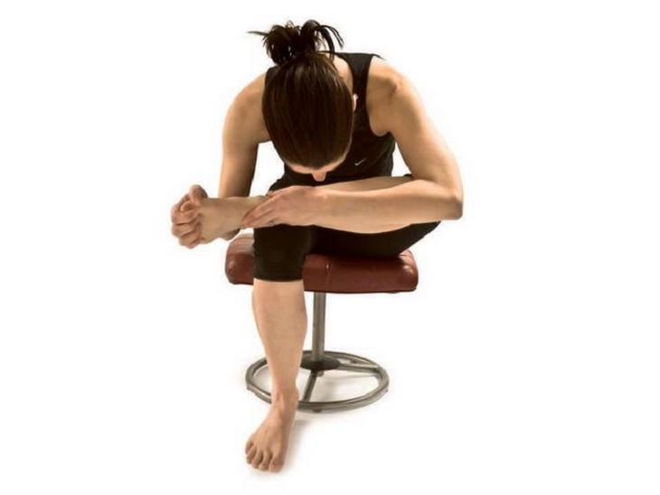 אישה כפופה על כיסא כשהיא אוחזת את אחת מרגליה על הברך של השנייה