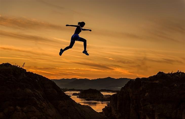צללית של אישה קופצת בין צוקים