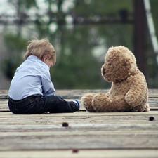 ילד קטן יושב מול בובת דובי