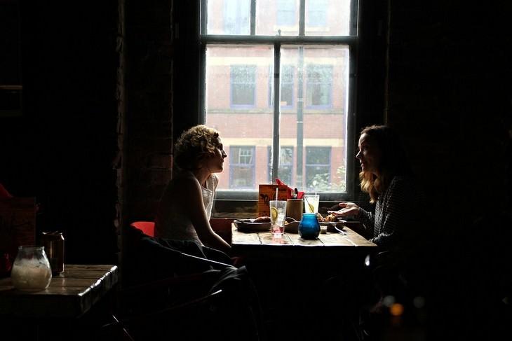 שתי נשים ליד שולחן משוחחות זו עם זו