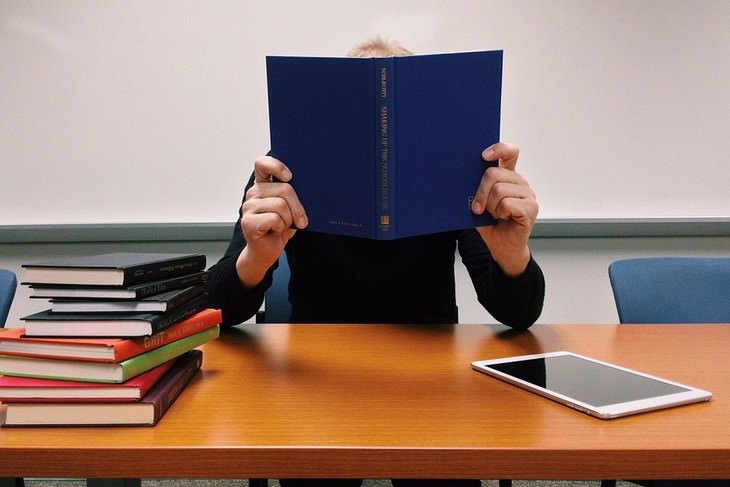 אדם יושב ליד שולחן מחזיק ספר מול פניו