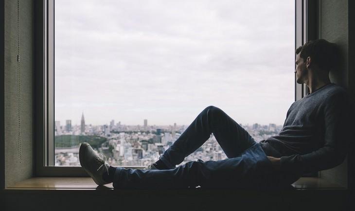 גבר יושב על אדן החלון ומסתכל החוצה