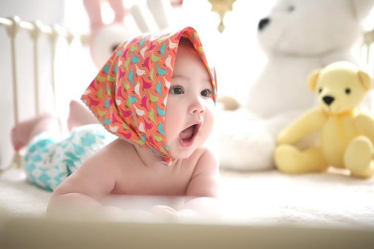 תינוקת שוכבת על הבטן מוקפת צעצועים