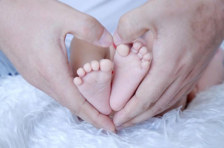 ידיים של הורים אוחזות בכפות רגליים של תינוק