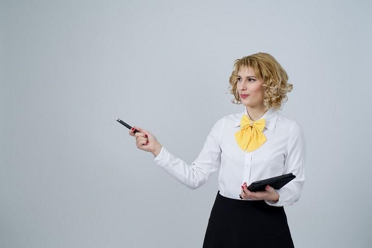 אישה עם מחברת ביד מצביעה לצידה הימני עם עט