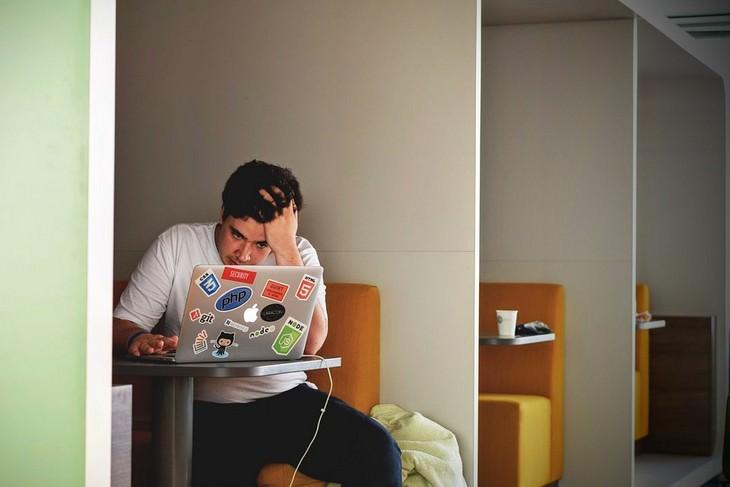 אדם מתוסכל יושב מול מחשב נייד