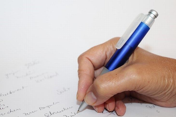 יד עם עט כותבת על דף