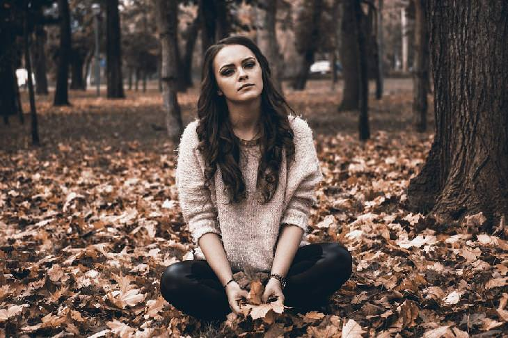 אישה יושבת עם מבט עגמומי בחורשה, מחזיקה עלי שלכת בידה