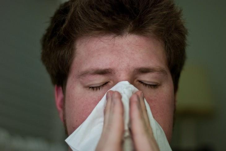 גבר מקנח את האף