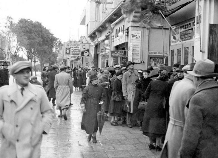 """החורף של שנת 1936 לא מנע מאנשים רבים להגיע לרחוב אלנבי ולהמתין בתור לקניית כרטיסים לקונצרט בכניסה לספריית """"רנסנס"""". צלם לא ידוע, מתוך ארכיון ביתמונה."""
