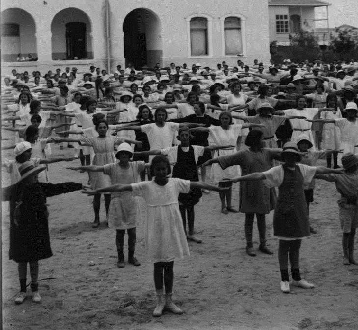 """תלמידות מתעמלות בחצר הגימנסיה העברית """"הרצליה"""" בשנת 1929. צילום: אריק מאטסון."""