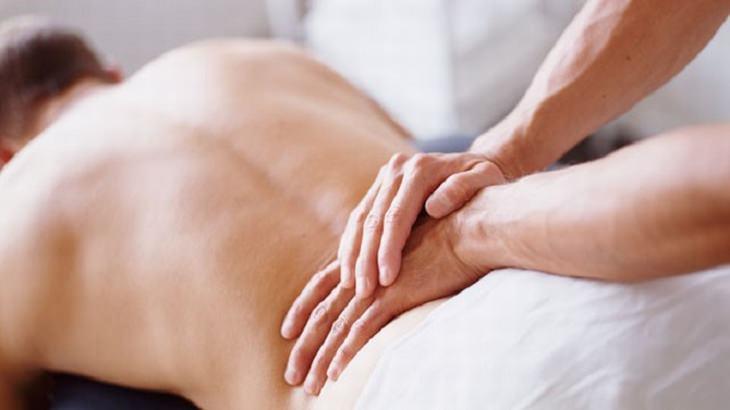 ידיים על גב של גבר מבצעות עיסוי עם כפות הידיים