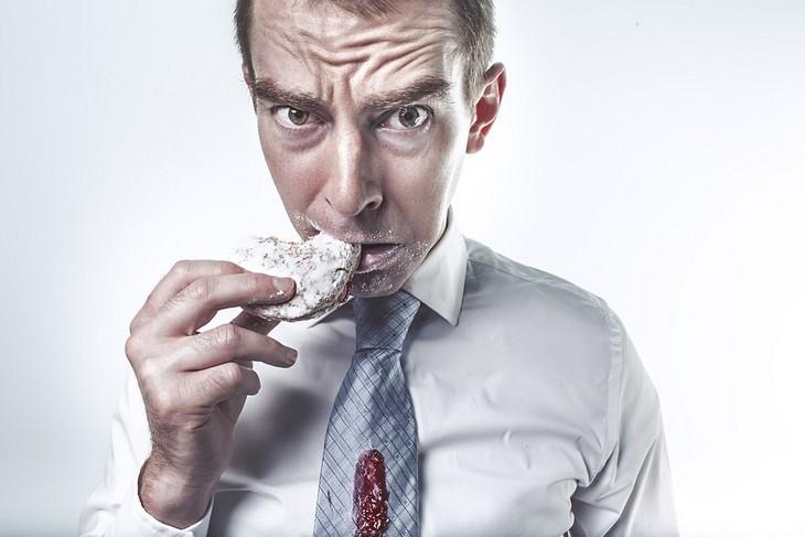 כתמי אוכל נפוצים והדרכים להסירם מבגדים: אדם אוכל עוגיה עם כתם ריבה על העניבה