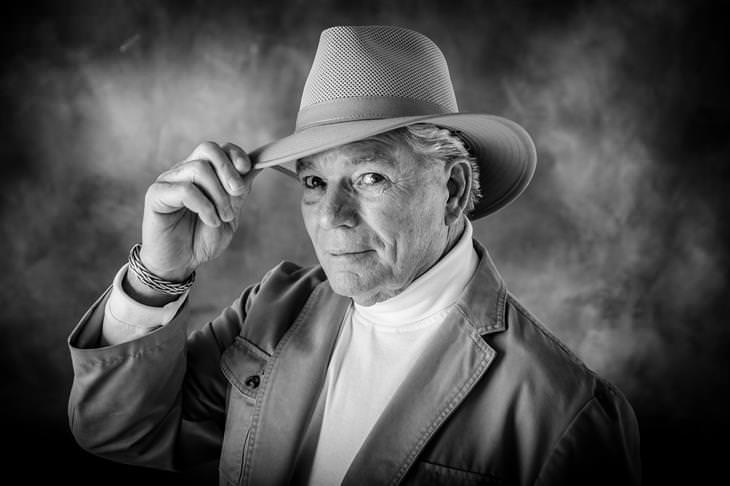 אדם מבוגר לבוש נאה ומחזיק בידו את שולי כובע המגבעת שעל ראשו