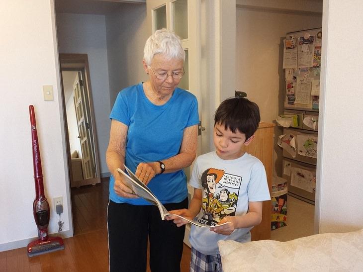 סבתא ונכד עומדים זה לצד זו וקוראים חוברת קומיקס